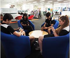Students enjoying reading Kindles